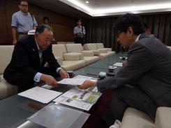 岡部市長に事業内容を説明する代表上岡裕(右)