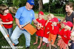 Ehrenamtlicher Mitarbeiter des NABU erklärt Kindern die Bauweise und Funktion eines Nistkastens