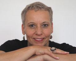 Foto von Beate Hablitzel, Frau mit kurzen grauen Haaren lächelt verschmitzt