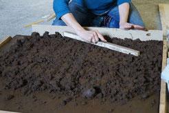 detailansicht die Künstlerin beim Stampfen einer Schicht dunkelbrauner isländischer Erde  mit einer Holzleiste beim Symposium  Korpulfsstadir Island