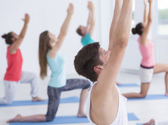 Eine Gruppe von fünf Menschen macht Rücken-Yoga. Bild Photographee.eu/Fotolia