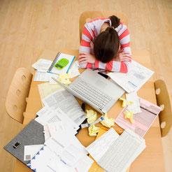 Jeune femme assise, la tête posée sur une table remplie de papiers, de dossiers et de post-it. La femme est brune et porte un pull rayé blanc et rouge.
