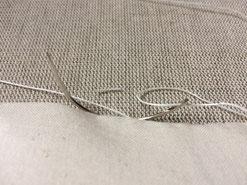 Couture à l'aiguille courbe et fil de lin d'une cuvette de bergère. Assemblage de la toile blanche et de la toile bisonne.