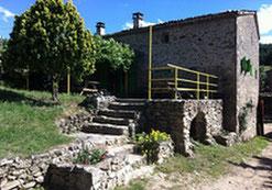 La façade du gite le long du chemin, un escalier de pierre qui monte sur la terrasse bordé d'arbres gite à louer et stage bien etre en ardeche
