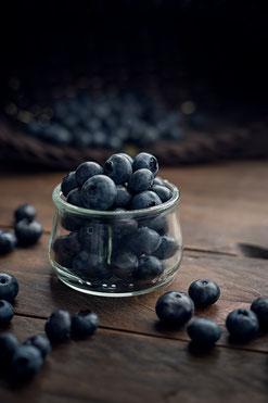 Blaubeeren im Glas auf Holztisch