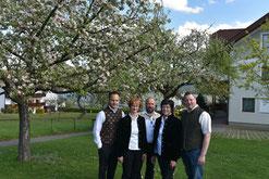 Familienfoto in unserem Garten mit blühenden Kirschbäumen im Hintergrund