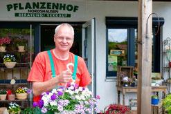 Frank Hartmann mit Blumenampel vor dem Eingang