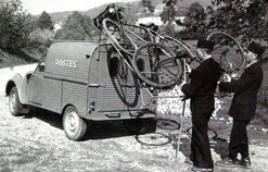 Deux facteurs posant des vélos sur le toit d'une 2CV fourgon des postes