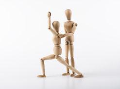 Zwei Holzpuppen stellen dar, wie im Personal Yoga ein Yoga-Schüler vom Yoga-Lehrer in einer Haltung korrigiert wird. Bild Clemens Schüßler/Fotolia