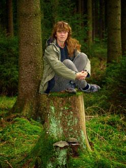 In einem Waldabschnitt sitzt Natur- und Kräuterpädagogin Claudia Kodet auf einem moosbewachsenen Baumstumpf.