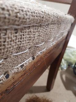 Restauration traditionnelle. Assise en ressorts et crin. Toile d'embourrure. Rabattage, piquage de la toile et des coins, pour donner sa forme définitive à l'assise