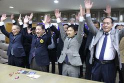 開催地決定に万歳し、笑顔を見せる桑江市長(写真手前左から2人目)=9日、沖縄市役所