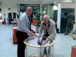 Herr Thomalsky (Sparkasse) und Herr Zitzmann (Schatzmeister des Kirchbauvereins) bei der Leerung des Spendentrichters