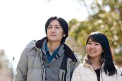 明るい日差しの中、笑顔で同じ方向を見つめる夫婦