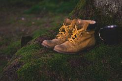 Schuhe und eine Tasse auf einem moosbedecken Fels