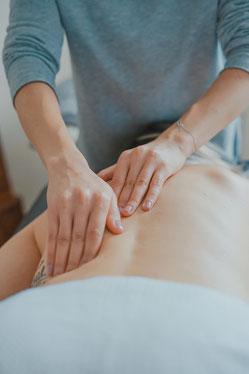 Abbild einer auf dem Bauch liegenden Person, die von einem THerapeut mit beiden Händen am Rücken massiert wird