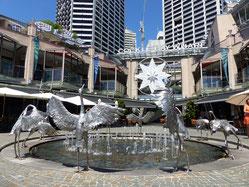 Une fontaine au ras du sol entourées de statues de fer représentant des hérons