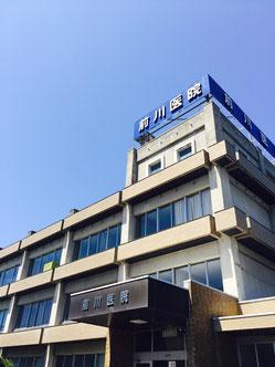 福井県福井市東郷にある内科・小児科・外科・整形外科(ペインクリニック)、前川医院の外観です。青空を背景に、建物を見上げています。ひまわりが咲いています。