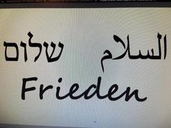 Maske mit Aufschrift Frieden in hebräisch, arabisch und deutsch