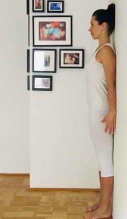 Katja Bienzeisler zeigt eine Yogaübung an der Wand für den Nacken