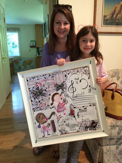 A student and her mother proudly display the art project created for the Kitsap Music Teachers Association Ribbon Festival.