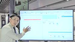 「ショールーム測定器前でソフトウエア画面を表示しながら説明するプレゼンター