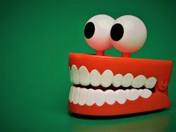 Gebiss mit rotem Zahnfleisch aus Kunststoff mit zwei Kulleraugen obenauf.