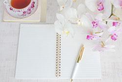 広げられたリングノートとボールペン。紅茶の入ったカップ&ソーサ。ランの花。