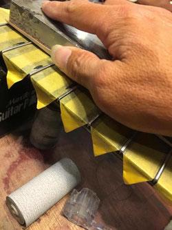 黄色いマスキングテープを貼った指板の上からやすりがけする作業
