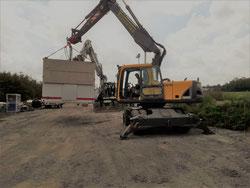 Ein Bagger hebt einen Baucontainer.
