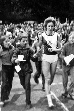 Die zweifache Olympiasiegerin Annegret Richter umlagert von jungen Fans.