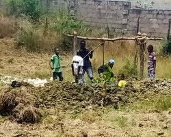 Am neu ausgehobenen Brunnen holen die angehenden Jungbauern Wasser für die Maispflanzen.