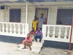 """Die ältesten Jungen sitzen vor """"Ihrem"""" Haus."""