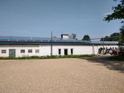 Blick auf zwei ehemalige Stallgebäude mit unseren beiden Solaranlagen. Im Vordergrund ist das Gebäude in dass das neue Ladenlokal zieht