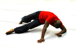 Marius Sawadogo habillé en rouge, au sol