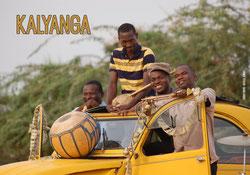 Les quatre membres souriants du groupe Kalyanga dans une 2 chevaux jaune