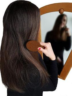Haarbürste Test, Frau mit langen glatten Haaren vor Spiegel mit Wildschweinborstenbürste