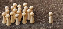 Holzfigürchen alle gegen einen oder einer steht vor allen