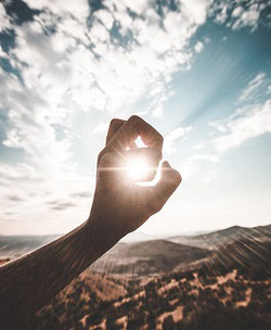 A hand, fingers curling, held out in front of the sun. The light of the sun shines through. The sky is blue with white clouds, and mountainous terrain stretches out ahead of the viewer.