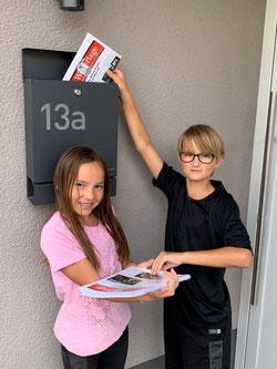 Svea und Tove verteilen mit ihrer Mutter Sandra Bennoit, Mitglied im Ortsrat Riegelsberg, die Wetterlage im Girsorsviertel.