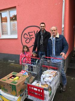 SPD Ortsvereinsvorsitzende Frank Schmidt mit seinen Kindern Leonie und Nico bei der Übergabe der gesammelten Lebensmittelspenden an Vorstandsmitglied der Tafel Horst Kalvas.