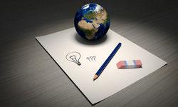 Une feuille de papier avec une ampoule dessinée, un crayon, une gomme et la mappe monde posés sur une table