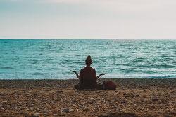 Une femme méditant assise en tailleur sur le sable face à la mer et au loin la ligne d'horizon