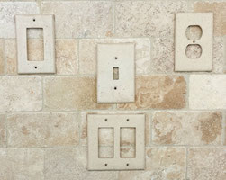Stone switchplates and outlet covers shown on a travertine backsplash.
