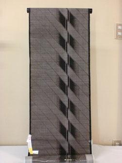縦横の糸を括り染めした糸を泥につけて織り上げた本場大島紬