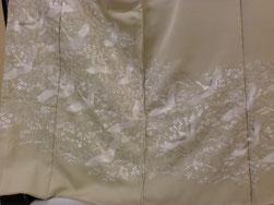 クリーム地に光沢のある白の刺繍糸で、飛び鶴を裾全体に刺繍した豪華な色留袖
