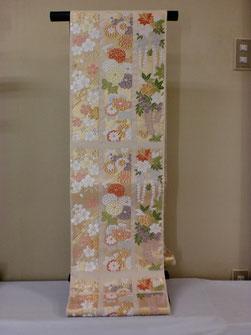 クリーム地に色糸の、バランスがかわいらしい特選唐織の袋帯です
