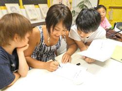 「両手いっぱいのありがとう」にサイン中のクーリカン智子さん