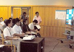 テレビ画面を通じて琉球大・池田教授の公開講座を聴く人たち=25日午後、市立図書館視聴覚室