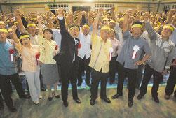 ガンバロー三唱で気勢を上げる仲井真氏(中央)と支持者=25日夜、屋内練習場